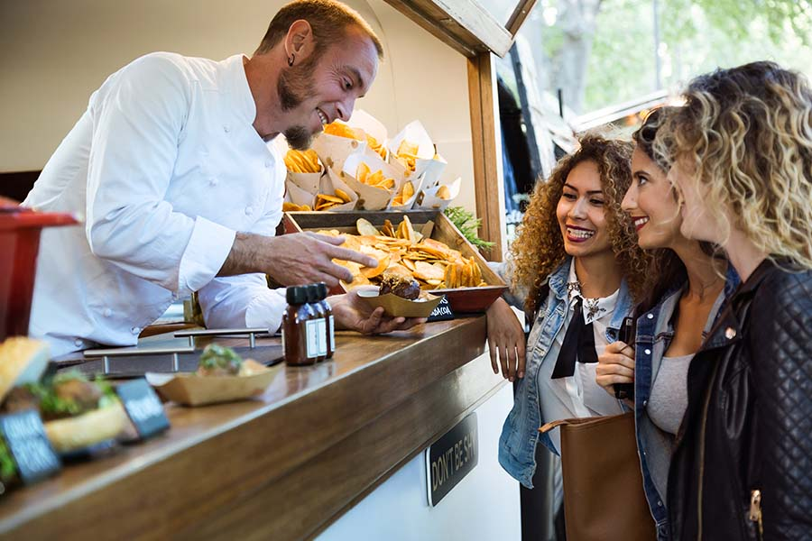 Food Truck Insurance - Young Friends Buying Food from a Food Truck at a Local Fair