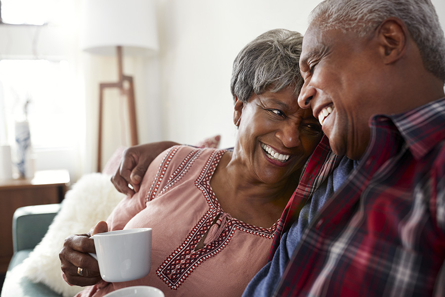 Medicare - Loving Couple Sitting on the Sofa at Home Relaxing with a Hot Drink