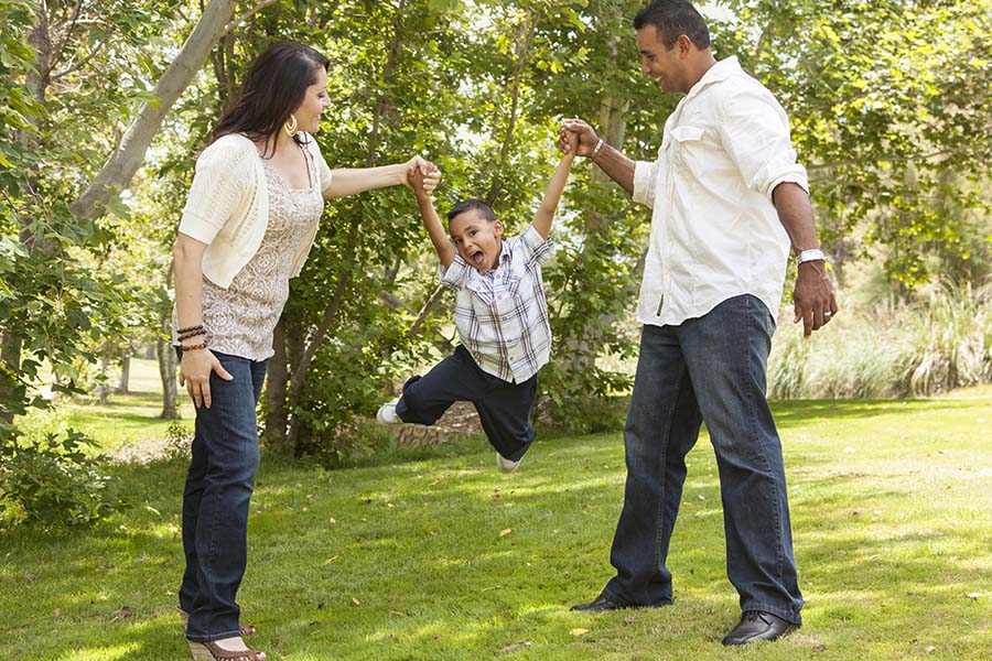 About Our Agency - A Mother and Father Are Swinging Their Son With Their Hands and Smiling at a Park on a Sunny Day