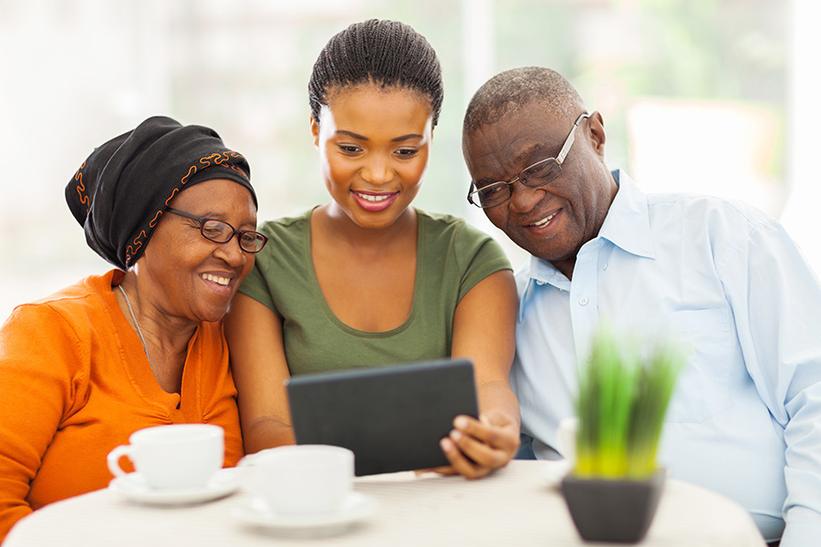 Client Center - Young Woman With Her Older Parents Showing Them How to Use a Tablet