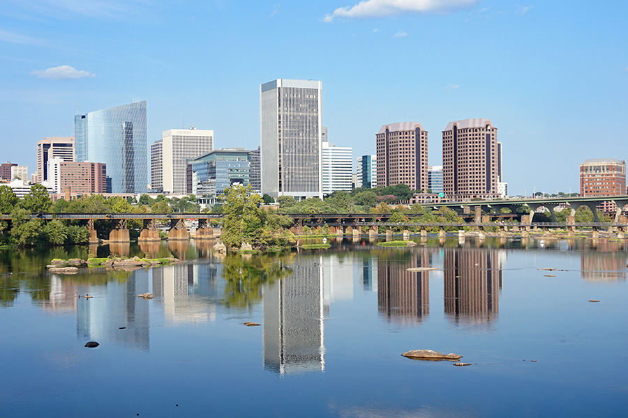Contact - Long Distance View of the Richmond Virginia Skyline Reflecting in the James Rivers and Displaying Tall Buildings and a Park