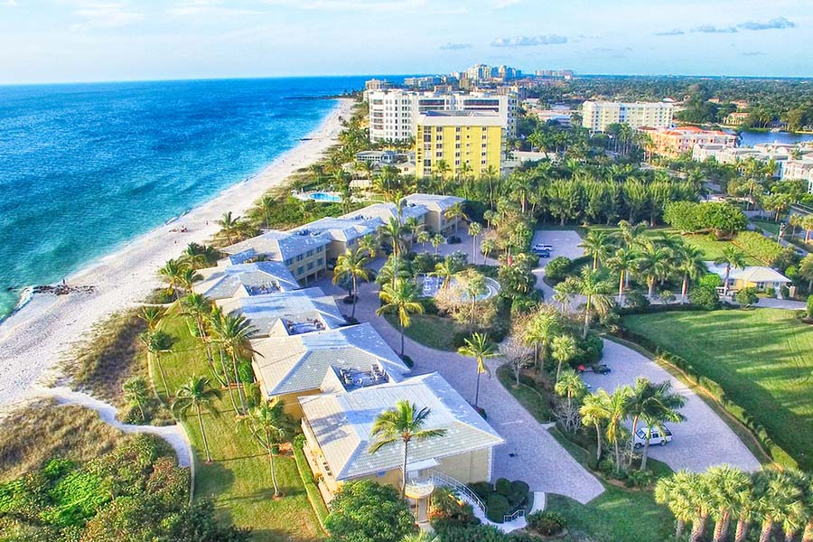 Homepage - Aerial View of Naples, Florida Displaying the Ocean and Beach by Buildings and Palm Trees