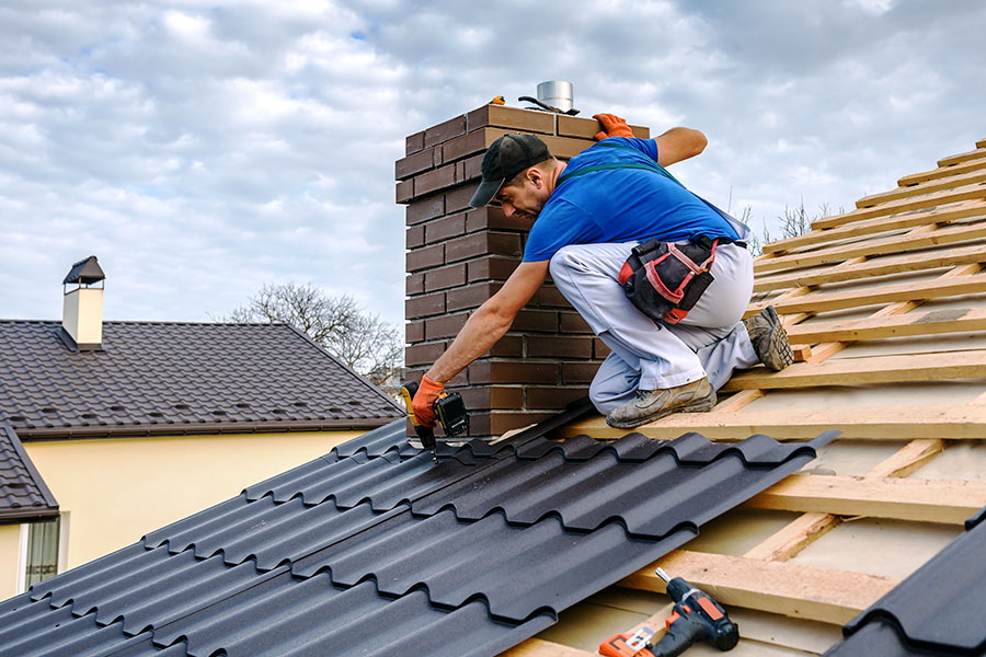 Roofer Insurance - A Professional Worker Installing Shingles on the Roof of a House on a Cloudy Day