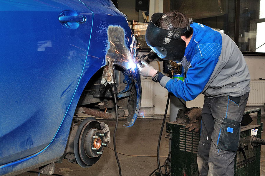 Specialized Business Insurance - A Worker Wearing a Heavy Mask Welding a Blue Car in an Auto Shop